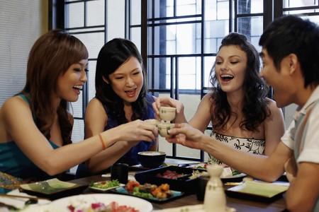 sake: Man and women toasting their drinks