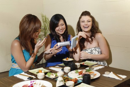 Woman holding an opened gift, friends laughing photo