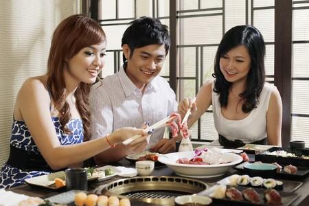Man and women enjoying food in a japanese restaurant photo