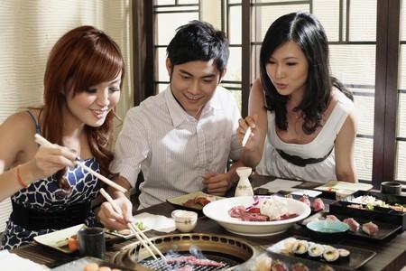weekend activities: Man and women grilling beef in a restaurant