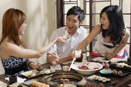 Woman feeding man with grilled beef, another woman watching photo