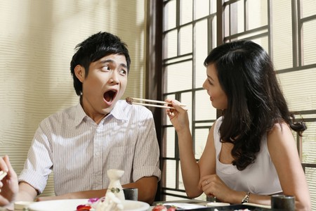 Woman feeding man with grilled beef photo