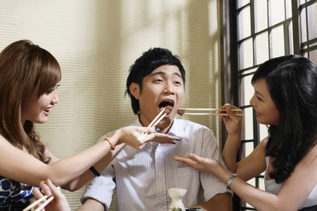 Two women feeding man with grilled beef photo