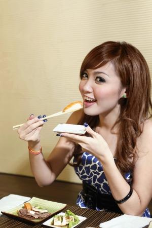 eating up: Woman eating sushi Stock Photo