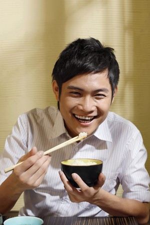 Man smiling while eating a bowl of rice