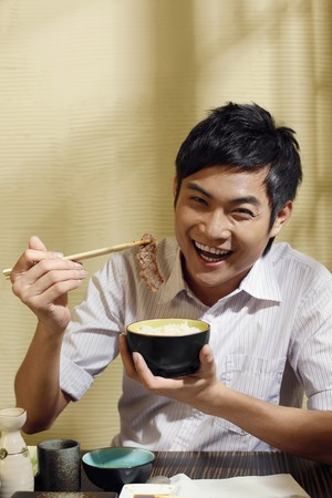 Man holding a bowl of rice and a piece of grilled meat photo