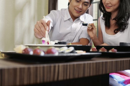 Man and woman eating sushi in a japanese restaurant photo