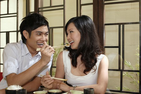Man feeding woman with sushi photo