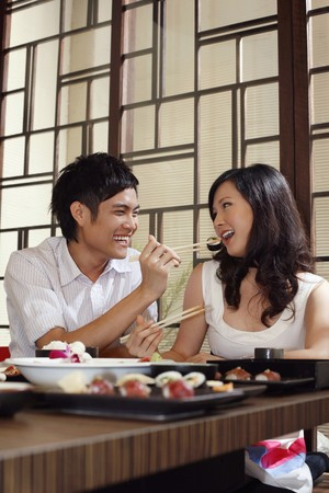 Man feeding woman with sushi photo
