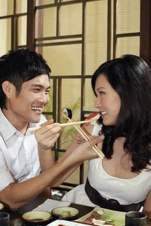 feed up: Man and woman feeding each other with japanese food Stock Photo