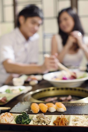 vegetables young couple: Sushi and a variation of vegetables, young couple eating in the background Stock Photo