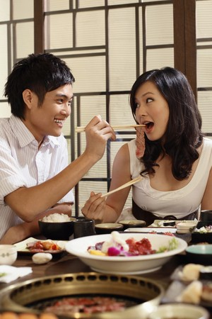 Man feeding woman with a piece of meat photo