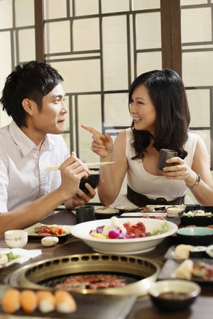 chopstick: Man and woman chatting while eating in a restaurant