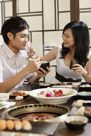 serviette: Vrouw man mond af te vegen tijdens het eten in een restaurant