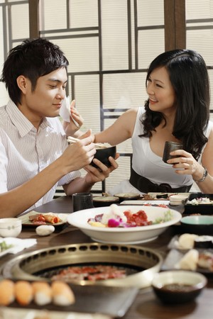 Woman wiping man's mouth while eating in a restaurant