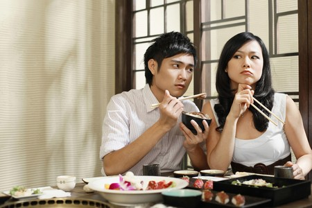 Man trying to feed his sulking girlfriend photo