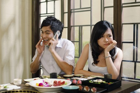 Man giggling while talking on the phone, woman sulking photo