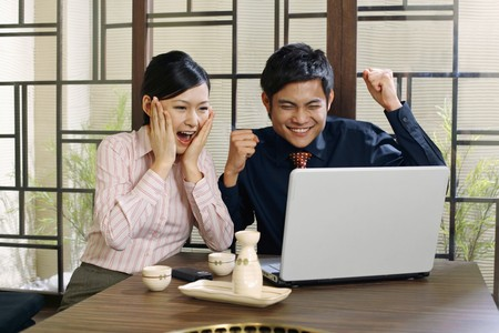 Business people jubilating while looking at laptop Stock Photo - 8149028