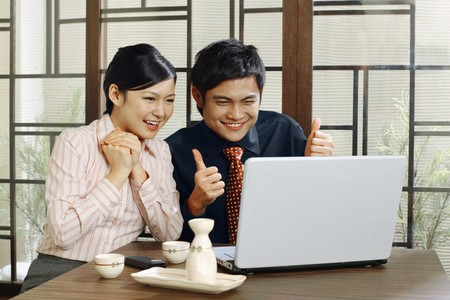 Business people jubilating while looking at laptop photo