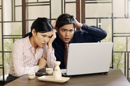 Business people looking at laptop in dismay Stock Photo - 8148782