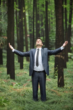 Businessman standing with arms outstretched in forest photo