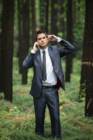 Businessman talking on the phone in forest Stock Photo - 8149159