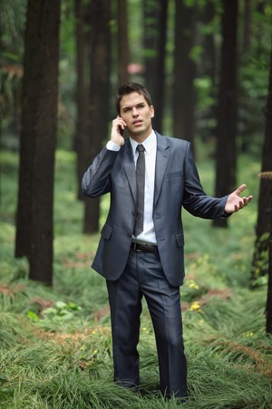 Businessman talking on the phone in forest photo