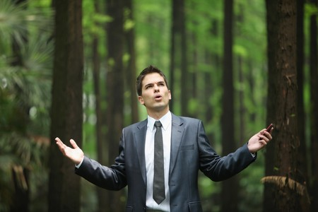 Businessman with mobile phone in forest Stock Photo - 8148714