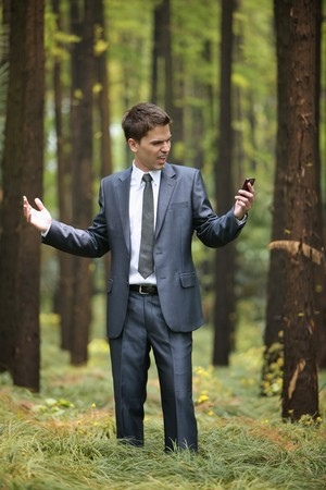 Businessman with mobile phone in forest photo