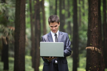 Businessman using laptop in forest photo