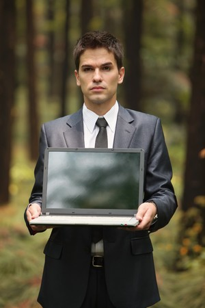 Businessman holding laptop in forest photo