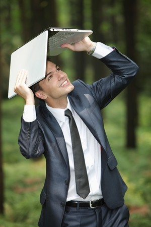Businessman shielding his head with a laptop photo