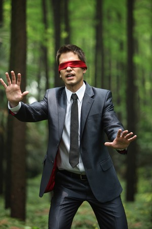 Businessman with blindfold walking aimlessly in the forest Stock Photo - 8149109