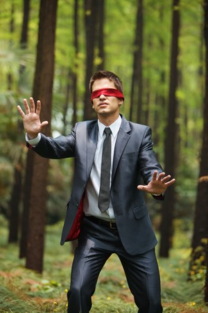 Businessman with blindfold walking aimlessly in the forest photo