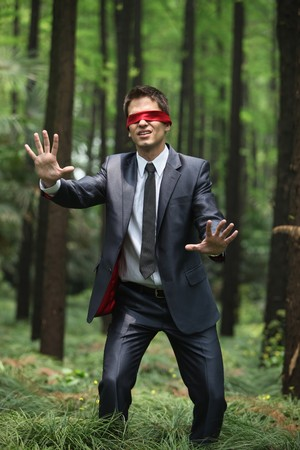 Businessman with blindfold walking aimlessly in the forest Stock Photo - 8149239