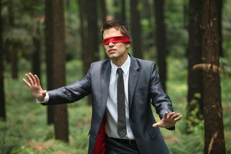 weakness: Businessman with blindfold walking aimlessly in the forest Stock Photo