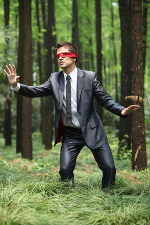 groping: Businessman with blindfold walking aimlessly in the forest Stock Photo