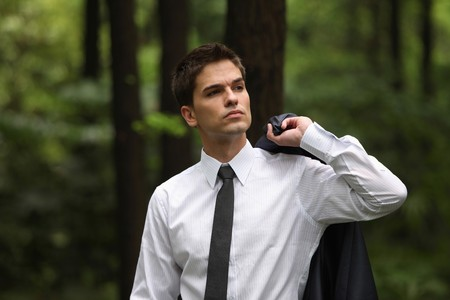Businessman holding coat in the forest photo