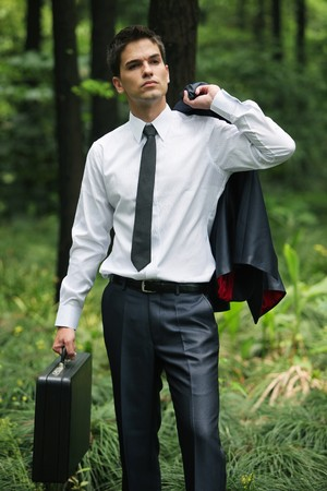 Businessman with coat and briefcase in the forest photo