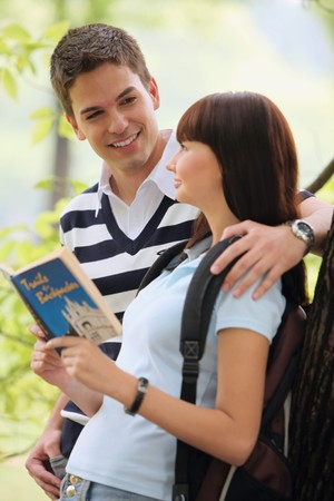 Man and woman reading book outdoors photo