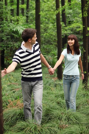 Man and woman holding hands in the forest