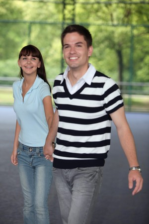 south eastern european descent: Man and woman holding hands in the roller rink