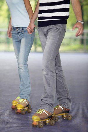 Man and woman holding hands while roller skating photo