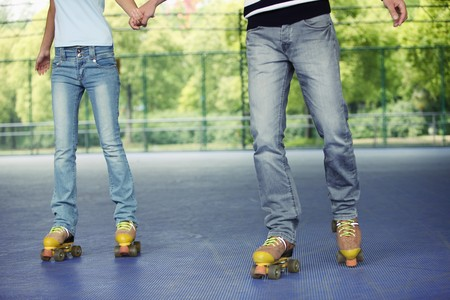 south western european descent: Man and woman holding hands while roller skating