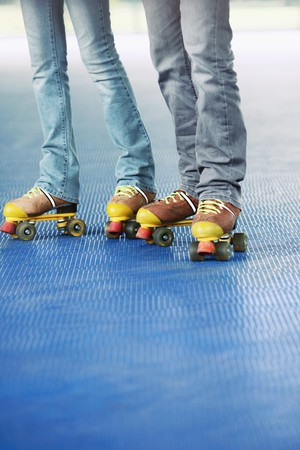 south western european descent: Man and woman roller skating together Stock Photo