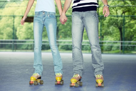 Man and woman holding hands while roller skating Stock Photo - 8149148