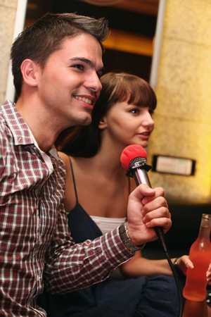 Man and woman at karaoke bar Stock Photo - 8149130
