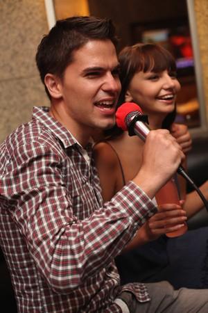 Man and woman at karaoke bar Stock Photo - 8149245