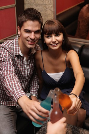 south eastern european descent: Man and woman toasting drinks at karaoke bar