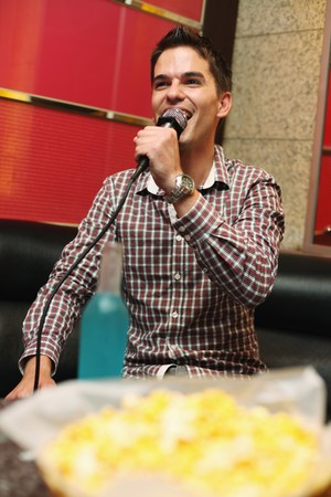 south western european descent: Man singing in karaoke bar